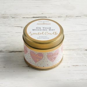 A coastal driftwood scented candle in a tin with pink hearts around the tin and on your wedding day on the lid