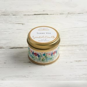 A scented candle in a tin with flowers around the side and thank you on the top