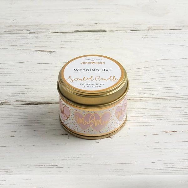 A scented candle in a tin with Wedding Day on the lid and around the candle Mr & Mrs in rose gold and rose gold hearts