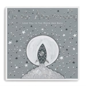 An anniversary card in tones of grey with silver foil details and embossing. A rocket blasting off in front of a big moon on a grey sky with embossed and foiled stars. On our anniversary love you to the moon and back