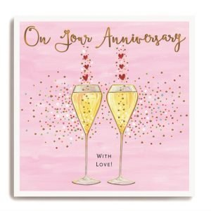 A pink anniversary card with two champagne glasses and lots of little hearts. On your anniversary with love