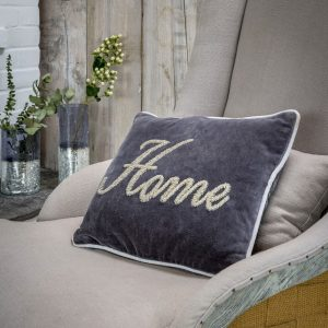 A grey velvet cushion iwth whit piping and home in beaded lettering
