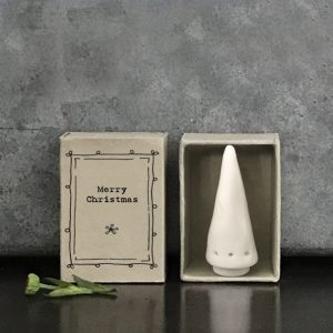 A small white porcelain Christmas tree in a box the size of a matchbox that says Merry Christmas on the front