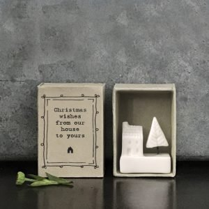 A white porcelain house and a tree in a matchbox that says Christmas wishes from our house to yours