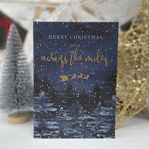 A lovely card to say Merry Christmas across the miles. With a fantastic image of a winter forest and Santa and his reindeer flying over the top of them.
