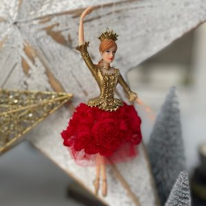 A ballerina princess hanging decoration. The princess has a dress with a gold bodice and a red lacey flowered skirt. She wears a gold crown.