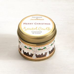 A Cinnamon and Clove mini candle with the words Merry Christmas printed on the tin. The label around the side of the tin has little Christmas Puddings on it.