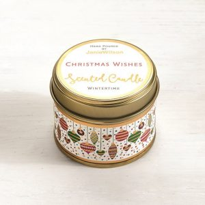 A sweet Wintertime mini candle with an image of little Christmas baubles printed around the side of the tin. The words Christmas Wishes are printed on the label on the top of the tin.