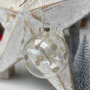 A clear glass bauble with gold glitter spots all over it.