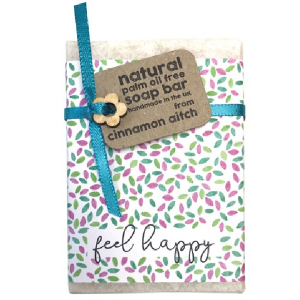 A lovely soap in a flowered paper with a silk ribbon and wooden flower The words Feel Happy are printed on the paper wrapper,