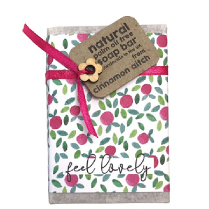 A lovely soap in a flowered paper with a silk ribbon and wooden flower The words Feel Lovely are printed on the paper wrapper,
