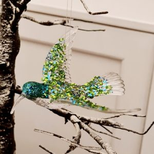 A Blue hummingbird decoration. An acrylic hanging hummingbird with blue glitter and irridescent sequins