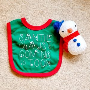 A green soft cotton babies bib in green with a red trim and velcro fastening with Santi Claus is coming to Toon