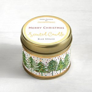 A candle with images of Christmas trees around the side and the label on the lid with the words Merry Christmas with the scent of Blue Spruce.