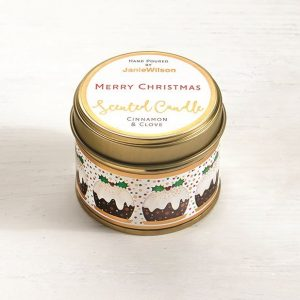 A Cinnamon and Clove candle with the words Merry Christmas printed on the tin. The label around the side of the tin has little Christmas Puddings on it.