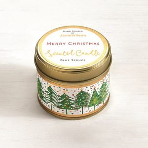 A mini candle with images of Christmas trees around the side and the label on the lid with the words Merry Christmas with the scent of Blue Spruce.