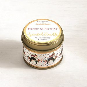 A Frankincense and Myrrh mini candle with an image of little Christmas penguins around the side.