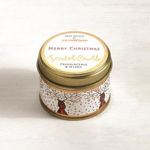 A Frankincense and Myrrh candle in a tin with images of reindeer around the side and the words Merry Christmas printed on the label.