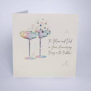 A lovely card from Five Dollar Shake with an image of two champagne glasses on it with extra jewels and sparkle. The words To Mum and dad Happy Anniversary Bring on the Bubbles is printed on it.