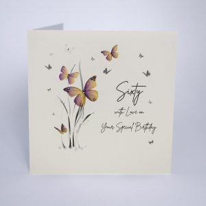 A beautiful card from Five Dollar Shake with an image of grass and butterflies and the words Sixty With Love on Your Birthday are printed on the card.