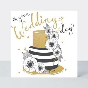 A lovely wedding card with an image of a black and gold tiered cake with flowers on it. The words On Your Wedding day are printed on the card.